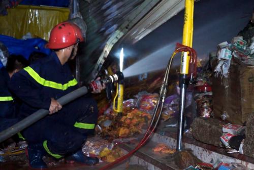 Cảnh sát chữa cháy căn nhà kinh doanh vàng mã. Ảnh: Xuân Mai