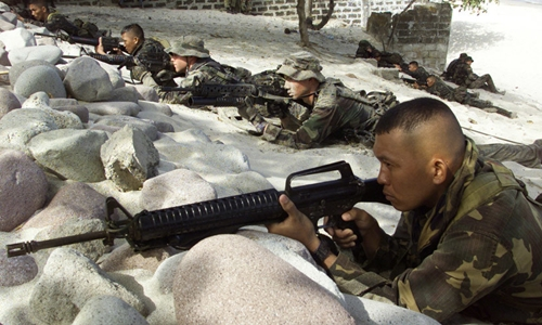 Filipino and U.S. marine soldiers take their position during a boat raid exercise at Ternate beach in Cavite province south of Manila on February 10, 2003. © Romeo Ranoco / Reuters