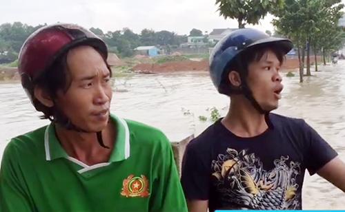 Hai anh thợ hồ cứu người phụ nữ bị nước cuốn. Ảnh: Nguyệt Triều