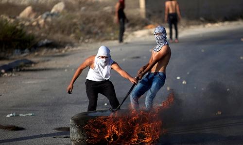 Người Palestine đốt cháy lốp xe trong cuộc đụng độ với binh sĩ Israel. Ảnh: Reuters.