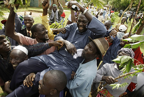 [Caption]Malik Obama is picked up by friends and family members as they celebrate Obamas victory in the U.S. election, at the familys homestead in Kogelo village, Kenya, Nov. 5, 2008. (Matt Dunham/AP)