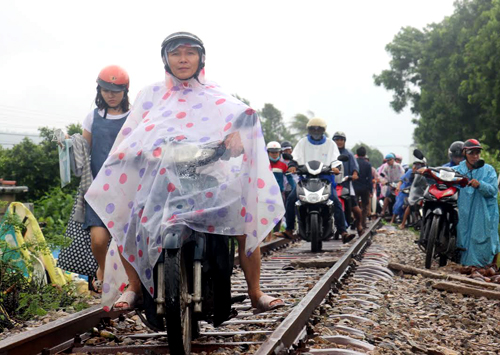 Người dân liều mình di chuyển tránh đường ngập lụt& trên đường ray tàu hỏa. Ảnh: Quy Nhơn.