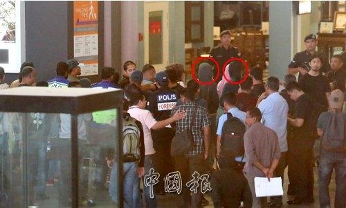 Hai nữ nghi phạm mặc thường phục thực nghiệm hiện trường vụ án trong sự giám sát của cảnh sát đội trọng án Malaysia. Ảnh: China Press