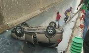 Nữ tài xế lao ôtô lật ngửa dưới kênh nước Hà Nội