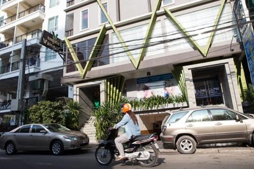 A motorist drives past V Hotel in Phnom Penhs Prampi Makara district on Thursday. (Hannah Hawkins/The Cambodia Daily)