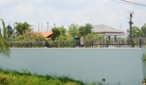 Ngoài bức tường cao bằng gạch kiên cố, căn biệt thự còn được bảo vệ bởi nhiều lớp kẻm gai phía trên. Ảnh: Nhật Lương