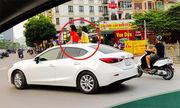 Hai bé gái ngồi trên cửa sổ trời ôtô chạy giữa phố Hà Nội