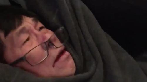 Ông David Dao bị các nhân viên an ninh hàng không thành phố Chicago kéo khỏi máy bay. Ảnh:
