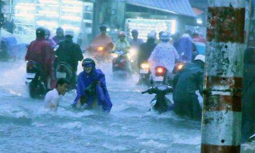 Nước cuốn trôi xe máy trong cơn mưa 2 giờ ở Sài Gòn