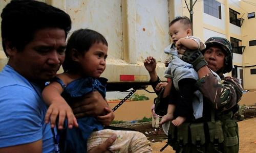Binh sĩ Philippines và nhân viên cứu hộ giải cứu hai trẻ em ở Marawi. Ảnh: Reuters