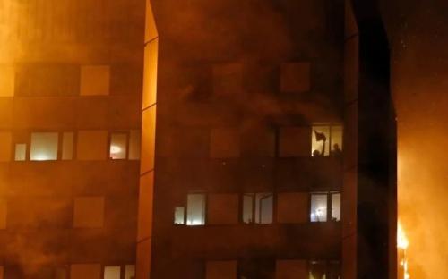 Người dân vẫy từ cửa sổ chung cư cháy. Ảnh: Telegraph