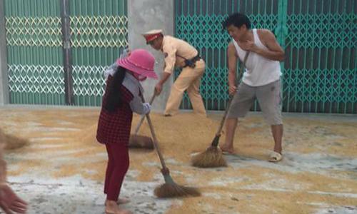 Cảnh sát giao thông giúp dân hốt lúa chạy mưa