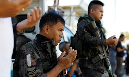 Cảnh sát Philippines cầu nguyện phía ngoài một đền thờ Hồi giáo ở Marawi ngày 25/6. Ảnh: Reuters.