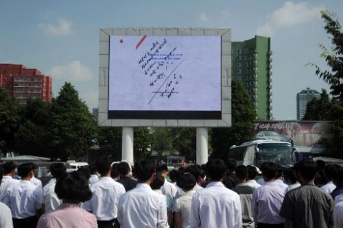 Người dân Bình Nhưỡng nhìn màn hình chụp lệnh phóng tên lửa do lãnh đạo Kim ký. Ảnh: AFP
