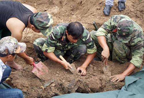 Bên dưới lốp đất sâu hơn 1m, lực lượng tìm thấy nhiều di vật còn sót lại của các chiến sĩ như: áo tăng che mưa của bộ đội, võng, cút áo..