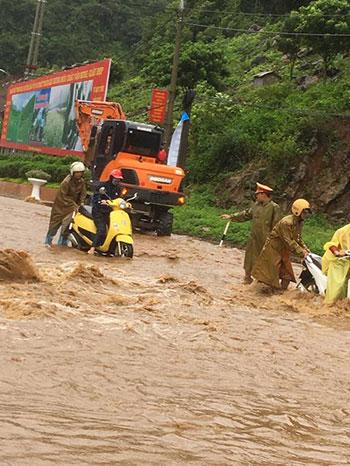 ên đoạn đường quốc lộ 6, nước lũ chảy xiết khiến người điều khiển xe máy lưu thông rất vất vả.